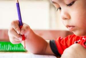 Preschool boy holding red pencil