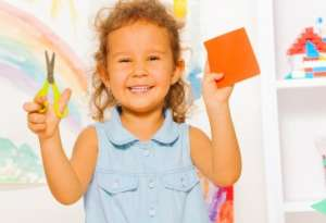 Smilling little girl holding scissors and a paper square