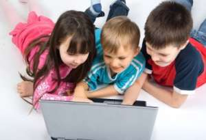 Three young kids laying on floor playing on laptop computer