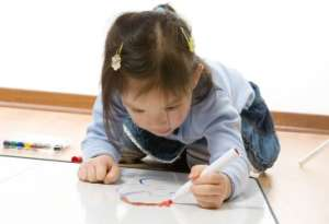 Young girl on floor painting picture