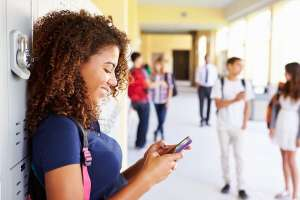 Teen girl standing at locker with cell phone