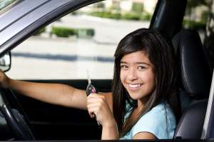 Teen girl holding car key and smiling