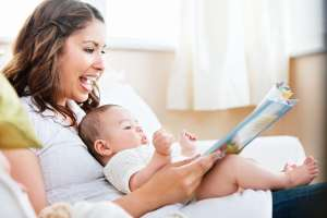 mom reading aloud to newborn baby