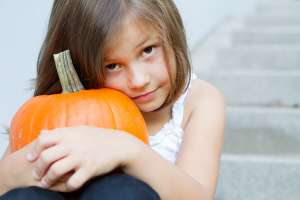 scared child with Halloween pumpkin