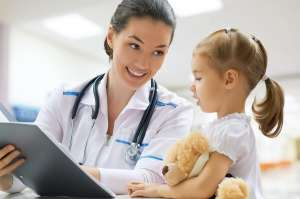 Doctor examining little girl at hospital
