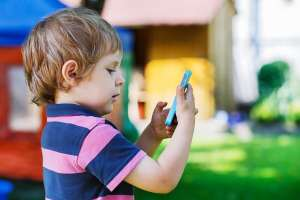 Young boy taking picture outside using smartphone camera
