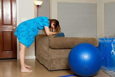 Pregnant woman leaning forward on couch