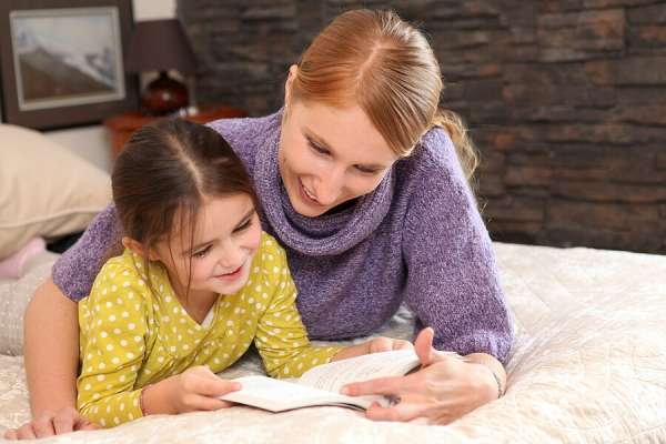 Summer Reading for Kids, Girl reading book with mother on a bed