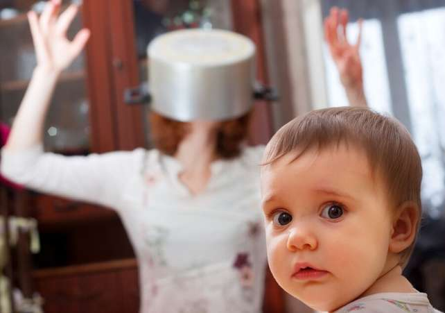 Alarmed child with crazy mom with pot on head in background