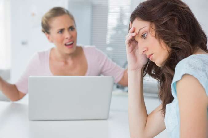 Two annoyed women sitting at a table on the computer