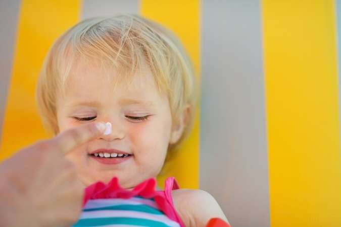 Applying sunscreen to toddler nose