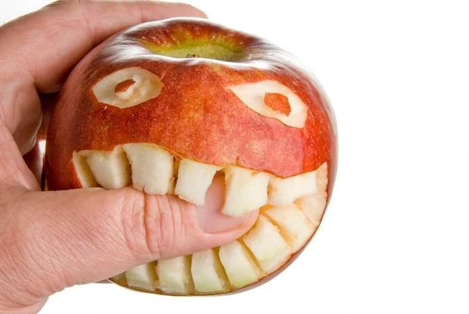 Funny face carved into apple, biting thumb against white back drop.
