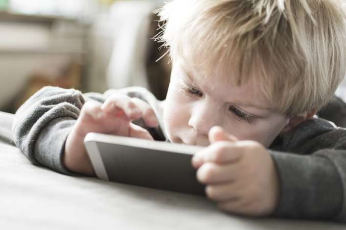Young blond boy using smartphone