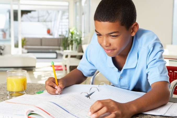 Boy sitting in kitchen doing homework