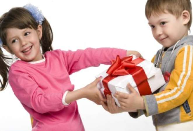 Young boy giving Valentine's Day gift to girl against white back drop