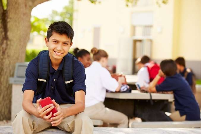 Boy on School Campus with Cell Phone