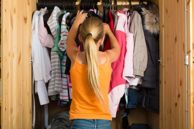 Young girl standing in front of closet looking for something to wear