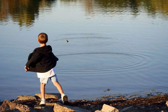 Summer Science for Kids, Child tossing rocks on a pond to learn physics of waves