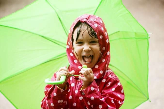Close up of child in raincoat holding umbrella