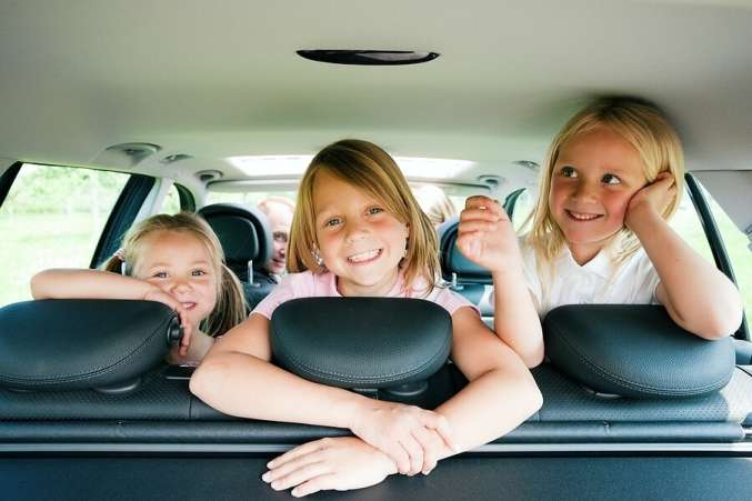 Three happy children in back of car