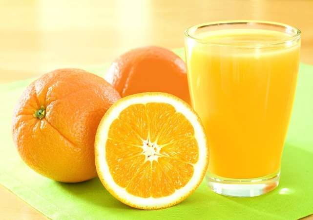 Cut oranges and glass of orange juice