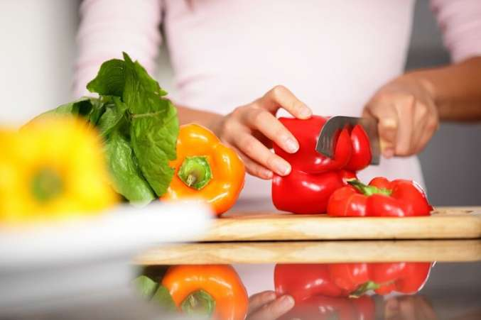Close up of red yellow and orange peppers with woman dicing in background