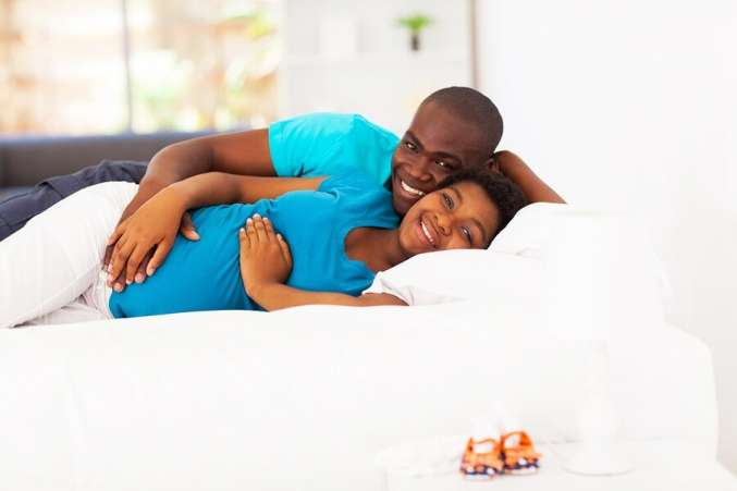 Happy expecting couple in bed