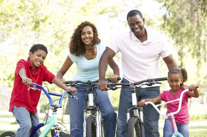 African American family riding bikes in the park
