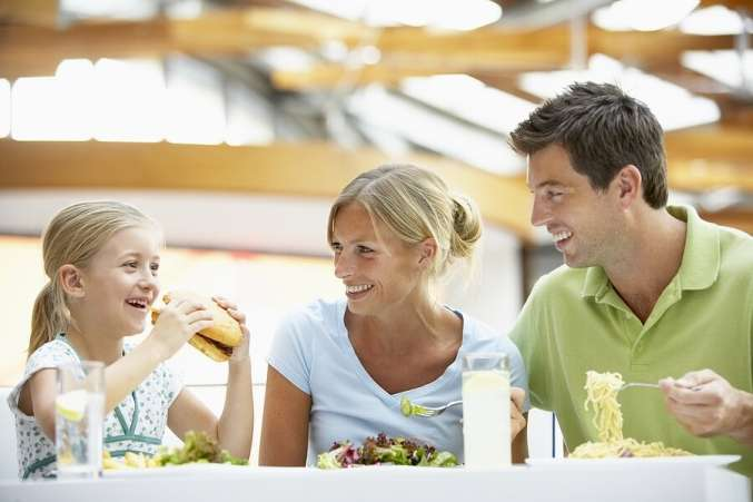 Young family eating lunch in food court