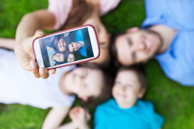 Family laying on lawn taking family selfie with smartphone