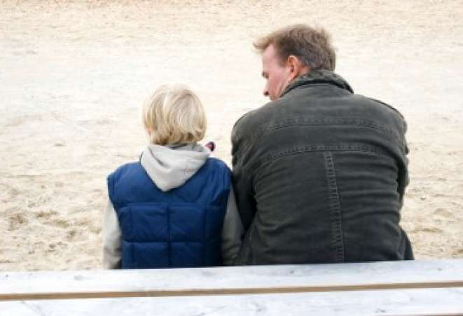 Back view of father and son talking on playground