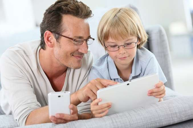 Father and son using smartphone and tablet