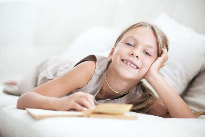 Young girl laying on sofa reading book