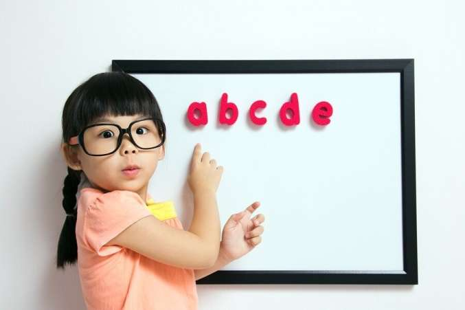 Little girl in glasses standing in front of white board with magnetic letters.