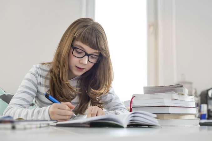Five ways to help your child focus and concentrate Mother Helping Daughter with Homework in Kitchen