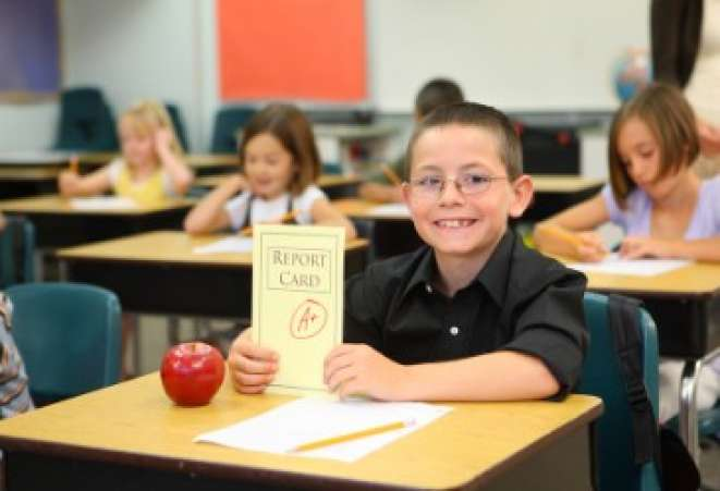 Smiling student holding up good report card