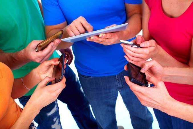Students holding cell phones and tablets on white background