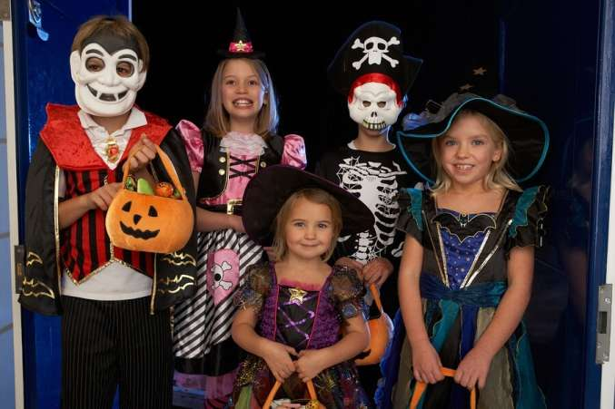 Groupd of kids dressed up and trick or reating on Halloween