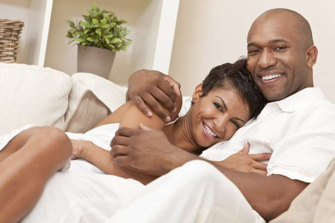 Happy African American Couple Smiling Sitting on Couch