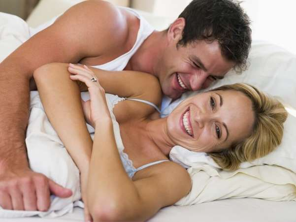 Smiling Happy Couple in Bed