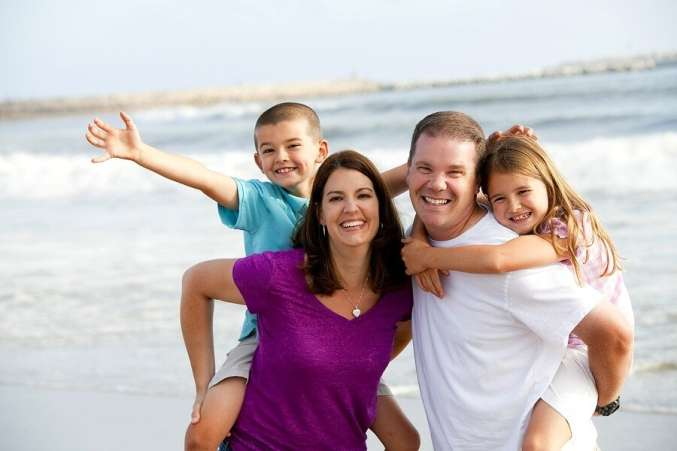 Happy family on vacation smiling at beach
