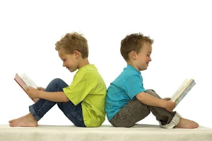 Two boys reading back to back against white background