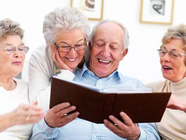 Happy elderly people looking at photo album