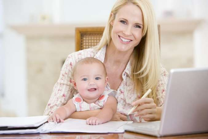 Happy working mother with smiling baby on lap
