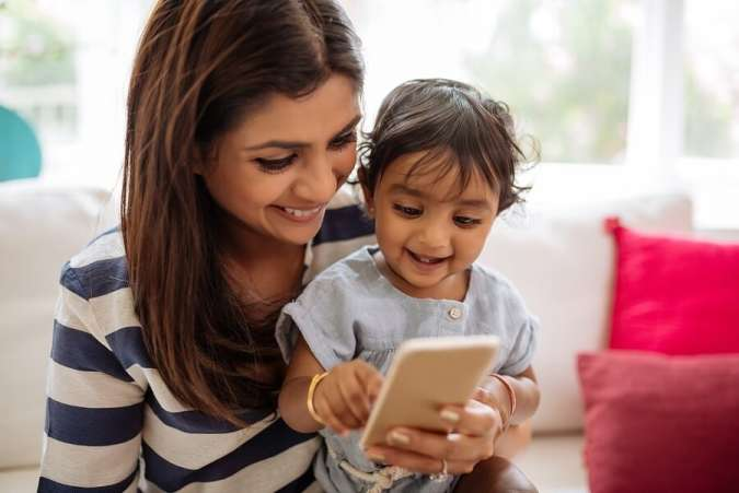 Indian mother and child playing on smartphone
