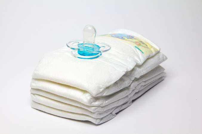 Stack of infant diapers and pacifier