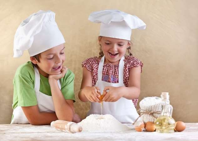 Two kids in aprons cracking eggs and baking