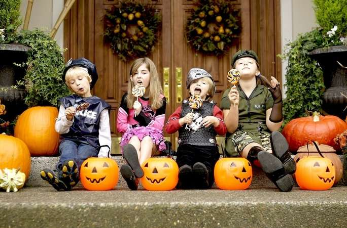 Kids dressed up for Halloween sitting on front stoop eating lollipops.