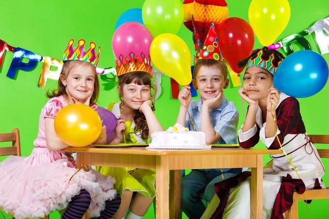 Kids sitting at table with birthday cake