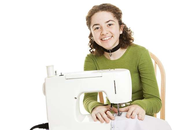 Teenager sitting at sewing maching